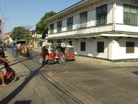 A street scene with horse-drawn carriages and motorbike-sidecar taxis.