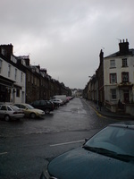 A steeply sloping street, wet after recent rain.