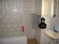A white-tiled bathroom.  A plastic shower curtain screens the bath, to the right is a sink with a mirrored cabinet over it.