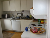 A kitchen, metal worksurfaces and white cabinets.  Pots and coffee-making equipment are scattered around.
