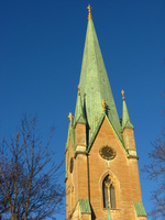 A church steeple roofed in pale green metal pokes up into a clear blue sky.  At lower left some bare trees are lit by the low winter sun.