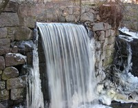 A stream flows over a stone wall, icicles hang around it.