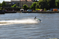 A jetski shoots across the picture from right to left, in the background are the far bank of the river and the railway station.