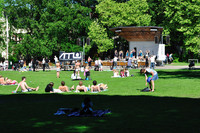 People lying in the sunshine on the grass in front of a stage.  On the stage several girls are dancing.