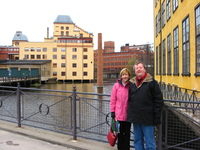 My parents standing on a bridge in front of part of a river, surrounded by former industrial buildings.  Mum and Dad are wearing big warm coats.