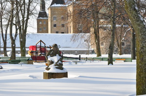 In the background part of a castle is lit by winter sun.  In front of it a childrens' playground sits among trees and snow.  In the foreground a statue of a woman looks down at the snow, her face lit by the reflected light.