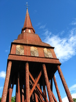 A red wooden belfry with shingled legs against a blue sky.