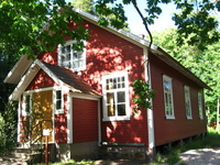 A small wooden building, painted red and white.