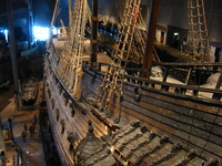 A wooden sailing ship in a museum buidling, people milling around down by the keel.
