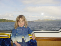 Eve standing in front of a window on a ferry, through the window can be seen the Firth of Clyde and the hills near Helensburgh
