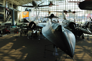 Various aircraft, mostly small, sit on the floor or hang from the ceiling of a large hall.  In the centre is an SR-71 Blackbird