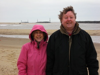 Mum and Dad standing on a sandy beach.  In the background are artificial rock reefs and the lagoons they have created.