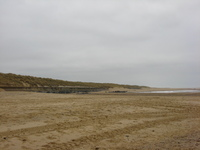 A sandy beach under grey skies.  Grassy dunes are on the left, stretching into the distance.