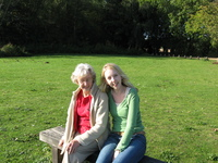 Granny and Eleanor sitting on a wooden bench on a lawn.